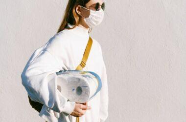 Frau mit Maske und Toilettenpapier unter dem Arm